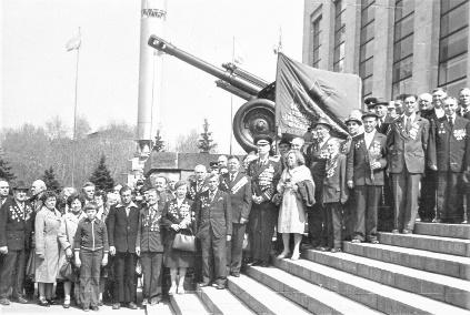 Ветераны с семьями на фоне своей легендарной пушки у боевого знамени на ступенях Музея вооруженных сил, 1975 год.