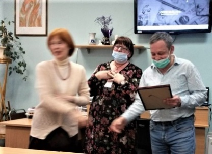 Г.В. Вершинина и заведующая библиотекой Е.Н. Борисова поздравляют художника Виктора Ефимова с наградой.